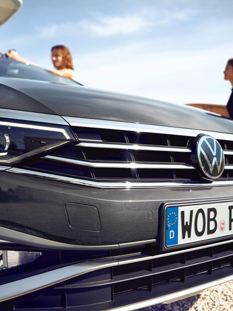 Volkswagen Passat Alltrack sulla spiaggia, primo piano sul frontale in direzione obliqua laterale, logo Alltrack sulla calandra, tavola da surf sul tetto, sullo sfondo due donne, una delle quali regge una tavola da surf sotto il braccio