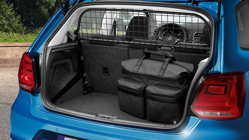 A detailed view of a luggage grid and a large bag in the trunk of a blue VW Polo 5 – Volkswagen Accessories