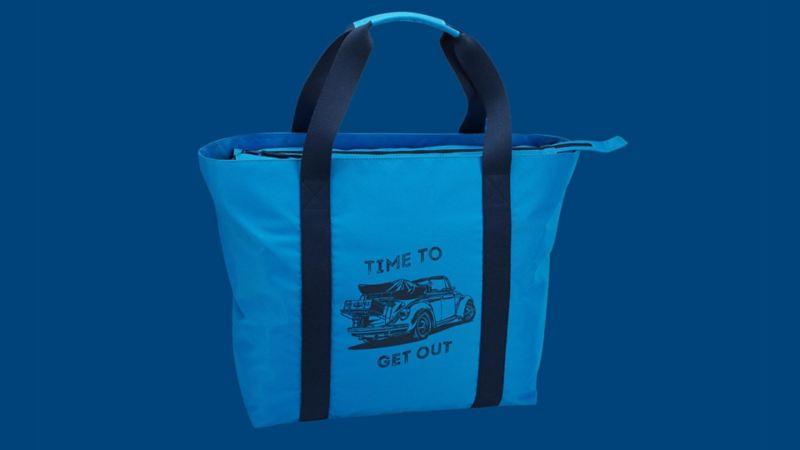 """Borsa da spiaggia blu della collezione Heritage di Volkswagen, con il disegno di un Maggiolino e la scritta """"Time to get out""""."""