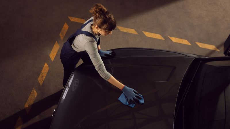 A VW service employee is cleaning the exterior of a VW car – care products