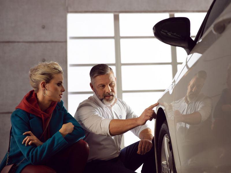 Un technicien Volkswagen montre à sa cliente les nouvelles pièces de carrosserie montéess sur sa voiture.