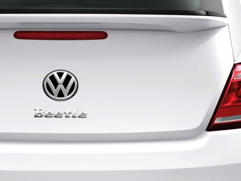 """A white VW Beetle with the logo """"Beetle"""" in chrome lettering on it – Volkswagen design"""