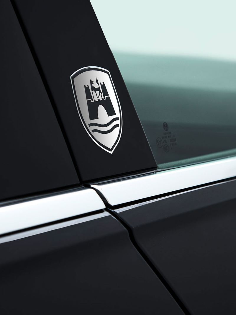 """A white VW car with the self-adhesive """"Wolfsburg"""" emblem on the door frame – Volkswagen Accessories"""