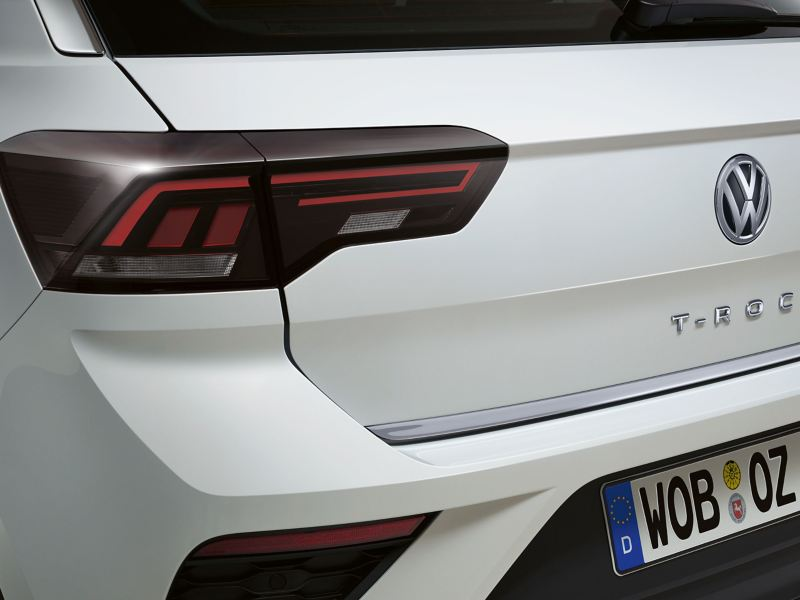 A white VW T-ROC with stylish LED lights and chrome lettering at the rear – Volkswagen Accessories