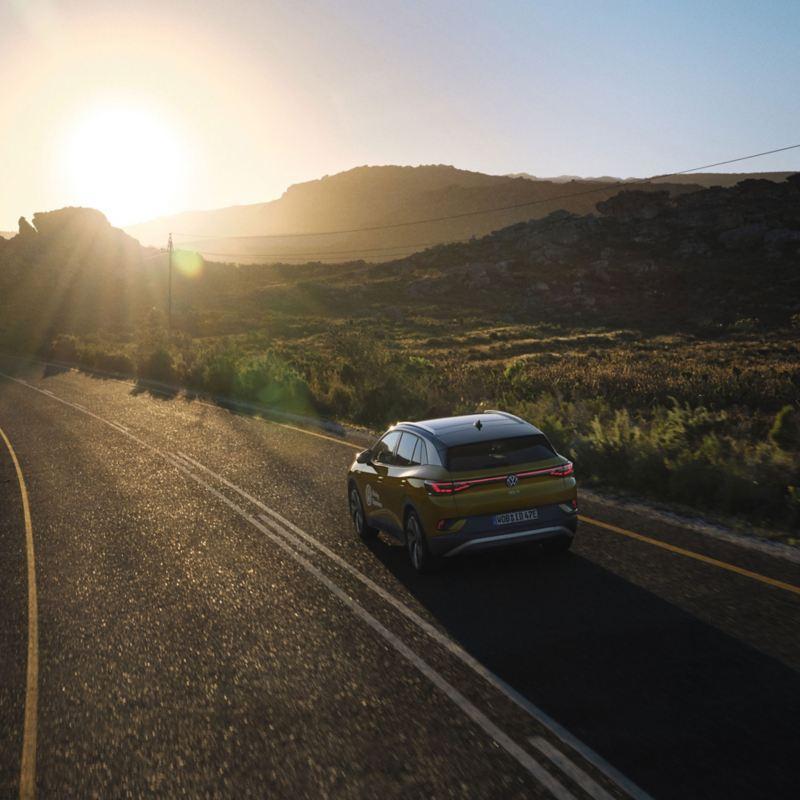 Ein Auto fährt im Licht der untergehenden Sonne auf einer Straße – Abenteuer im Volkswagen