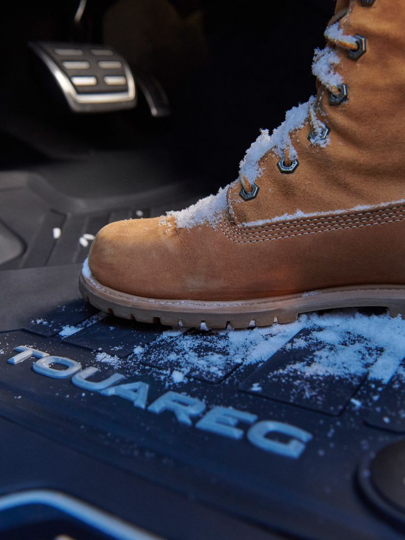 A snowy hiking boot on Volkswagen Accessories Rubber floor mats in a VW Touareg