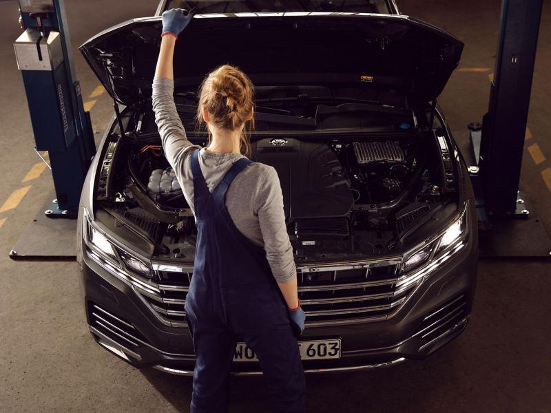 Une technicienne Volkswagen inspecte un véhicule dont le capot est ouvert - Pièces d'origine