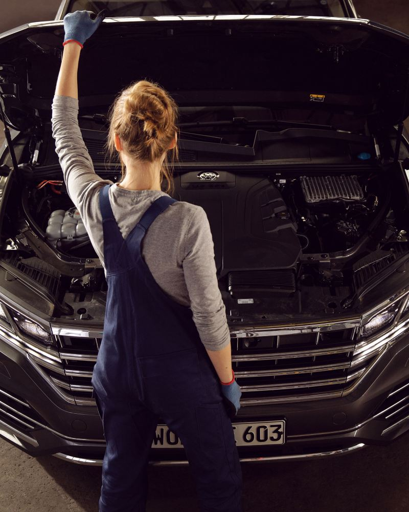 A VW service employee in front of a VW car with open bonnet – Genuine parts