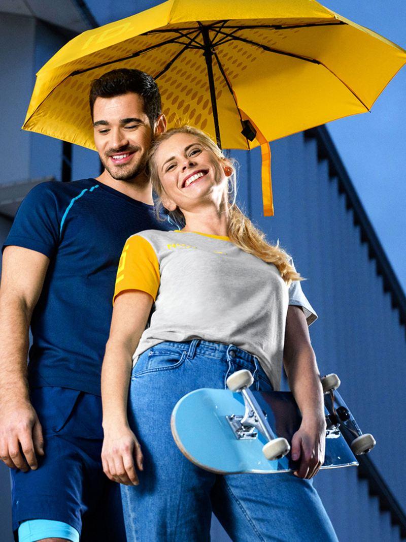Ein lachendes Pärchen mit moderner ID. Kleidung unter einem gelben Regenschirm – VW Merchandise