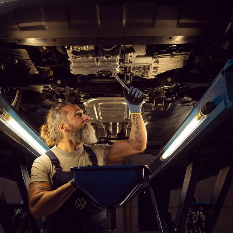 A VW service employee measures the tread depth of a VW car