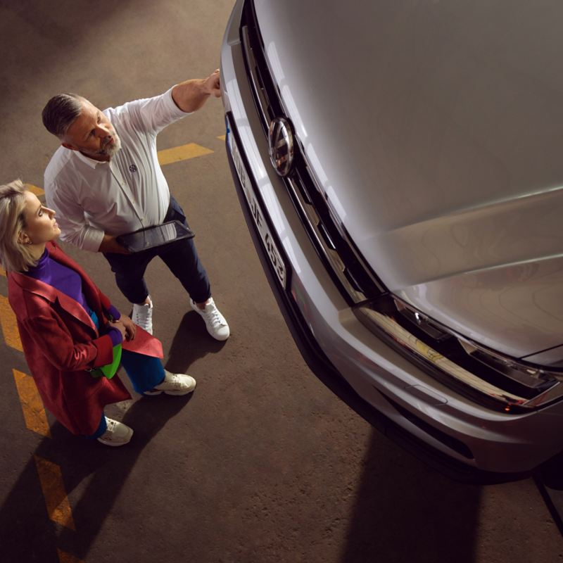 Eine Kundin und ein VW Servicemitarbeiter sprechen über ihr Auto – Inspektion und Reparatur