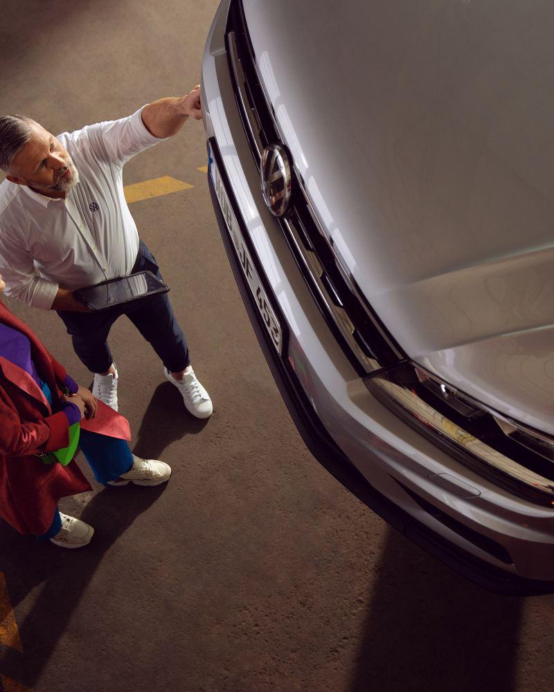 Eine Kundin und ein VW Servicemitarbeiter reden über ihr Auto – Inspektion und Reparatur
