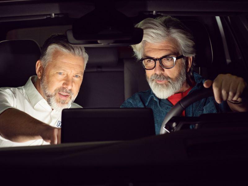 Ein VW Servicemitarbeiter und ein Kunde prüfen die VW Kundeninformationen