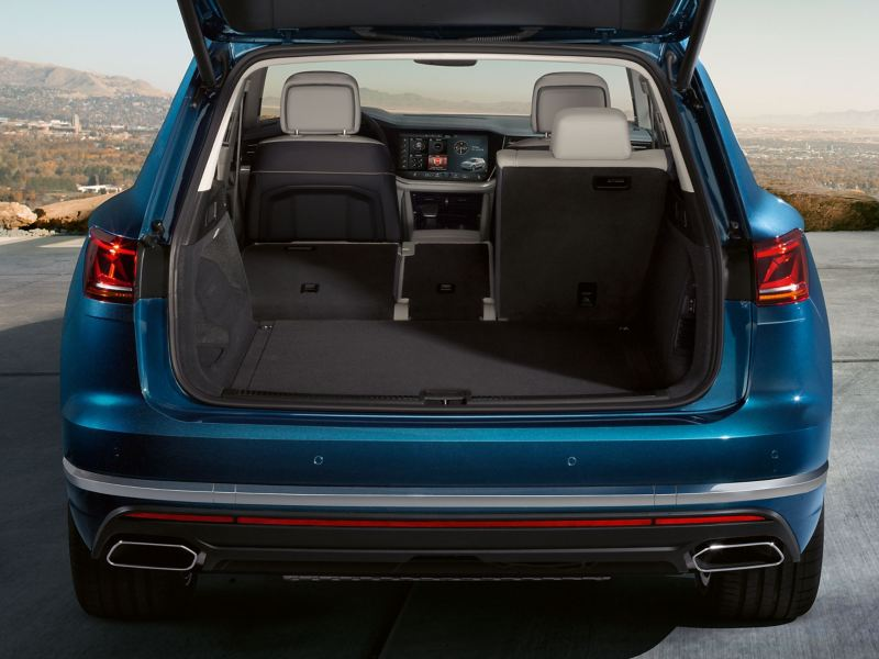 A blue VW car with open luggage compartment and folded down seat – Volkswagen luggage compartment solutions