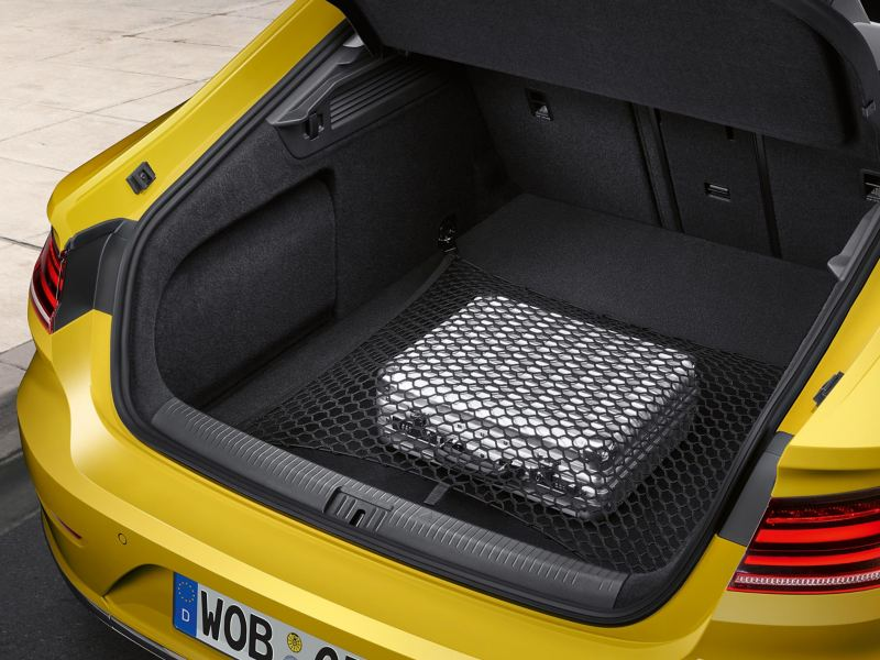 A yellow VW car with open luggage compartment and luggage inside in a baggage net – Volkswagen luggage compartment solutions