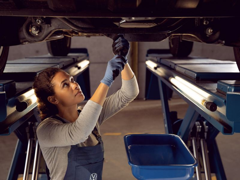 A VW employee changes the engine oil of a VW car – Oil Service