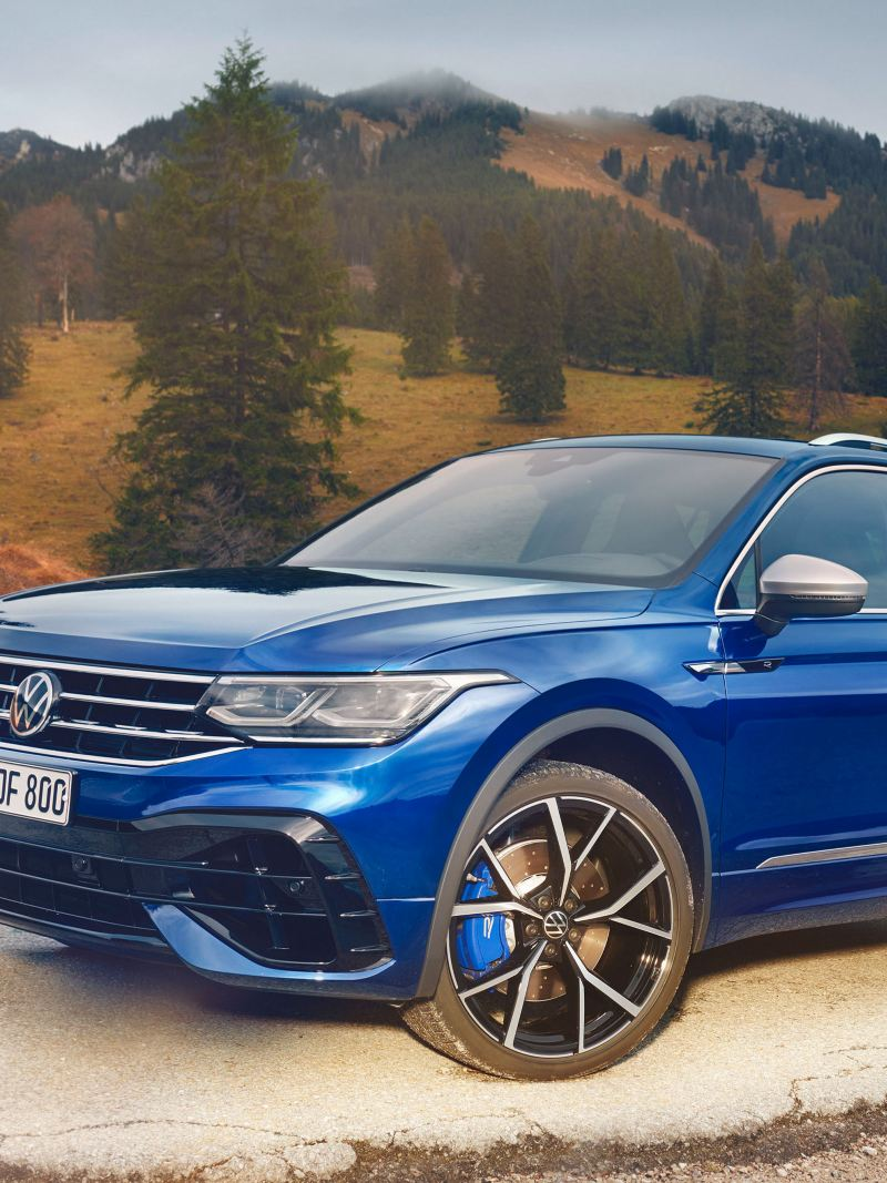 The VW Tiguan R in blue parked in front of a scenic backdrop
