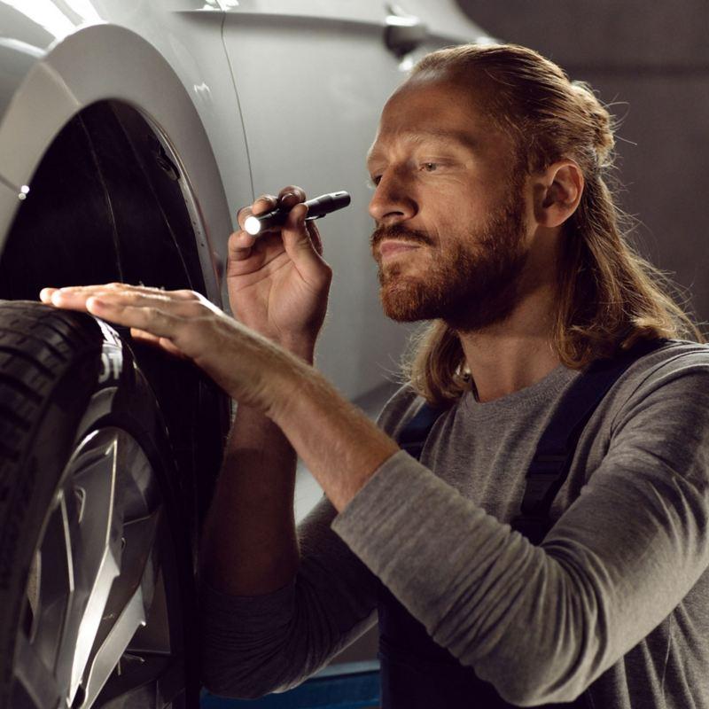 Ein VW Servicemitarbeiter inspiziert die Reifen eines Volkswagen