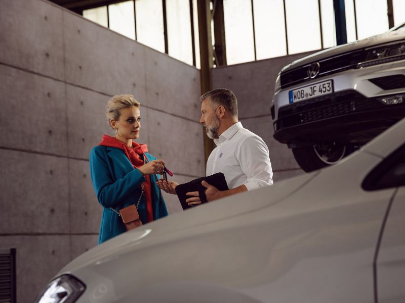 A customer hands over his vehicle keys to the VW service employee – Volkswagen Checks