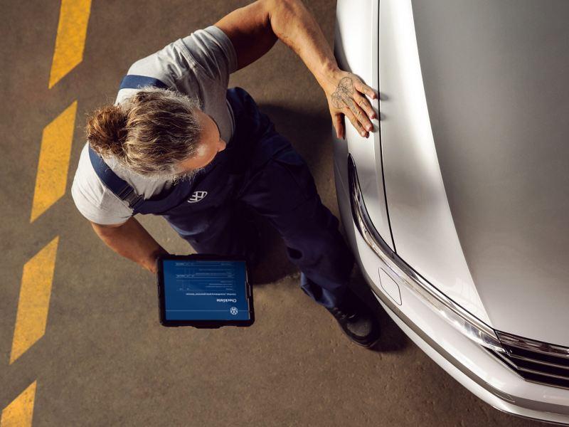 Ein VW Servicemitarbeiter prüft ein Volkswagen Auto in der Werkstatt