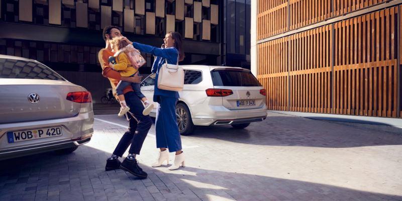 Familia joven sonriendo con una niña en brazos junto a un Passat plateado y un Passat GTE blanco