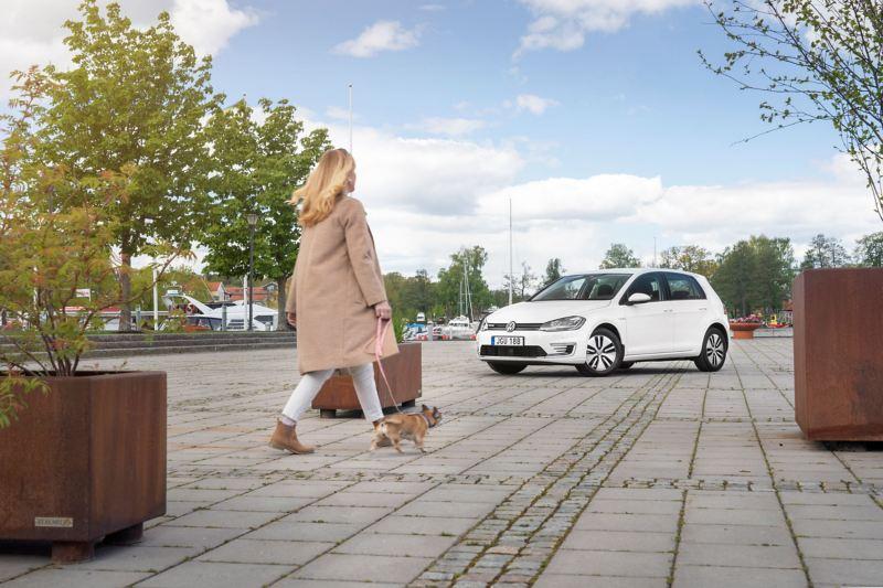 Kvinna med hund framför en VW e-Golf