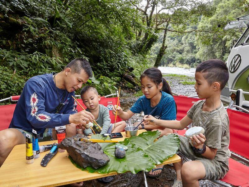 車主與三個孩子在山林間畫畫。