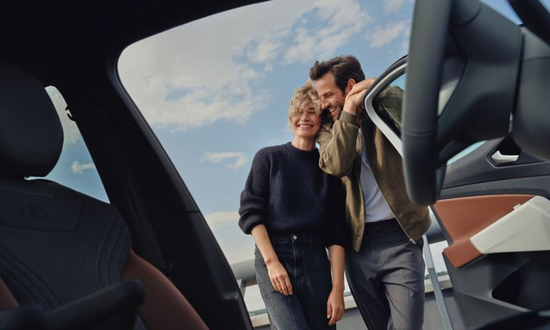 A couple leans against the open door of a car.