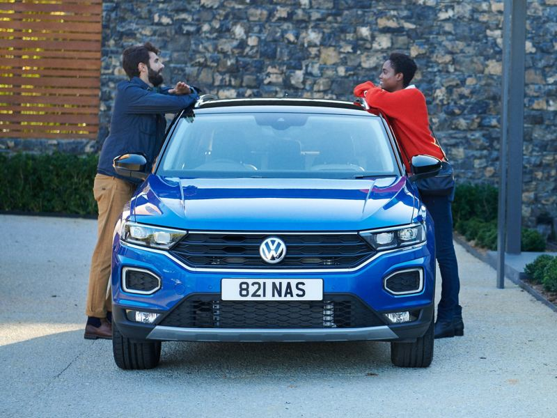 A couple standing on either side of a T-Roc