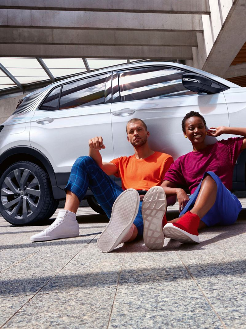 A couple sat on the floor next to a VW T-Cross