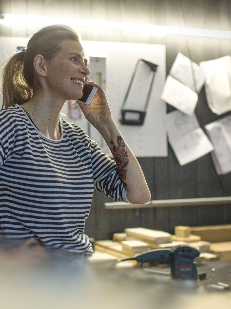 Eine Frau steht an einer Werkbank und telefoniert mit dem ServicePlus Notdienst.