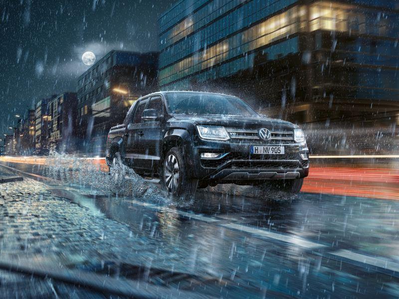 L'Amarok roule de nuit dans une ville, sous la pluie. De l'eau éclabousse sur le côté.