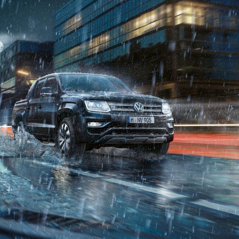 De nuit et sous la pluie, l'Amarok circule de façon dynamique dans une ville. De l'eau gicle sur le côté.