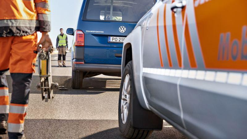 Volkswagen Transporter na drodze. W oddali widoczny mężczyzna w kamizelce odblaskowej.