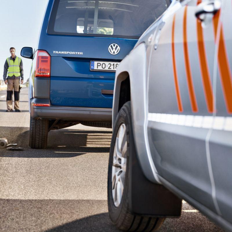 Dwóch mężczyzn stoi obok Volkswagen Transporter Furgon.