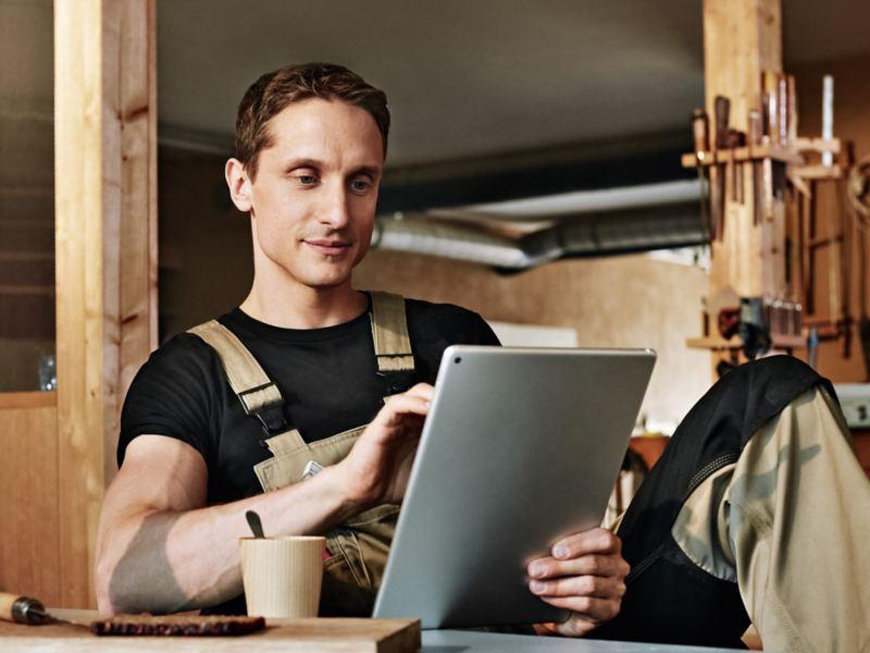 Ein Schreiner schaut auf sein Tablet.