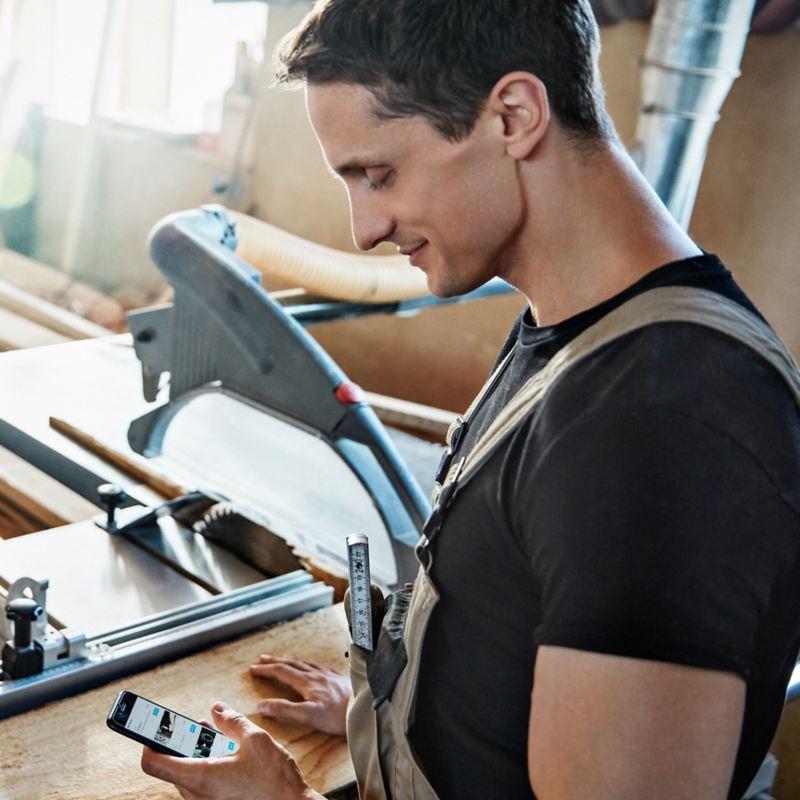 Ein Mann betrachtet in einer Werkstatt sein Smartphone