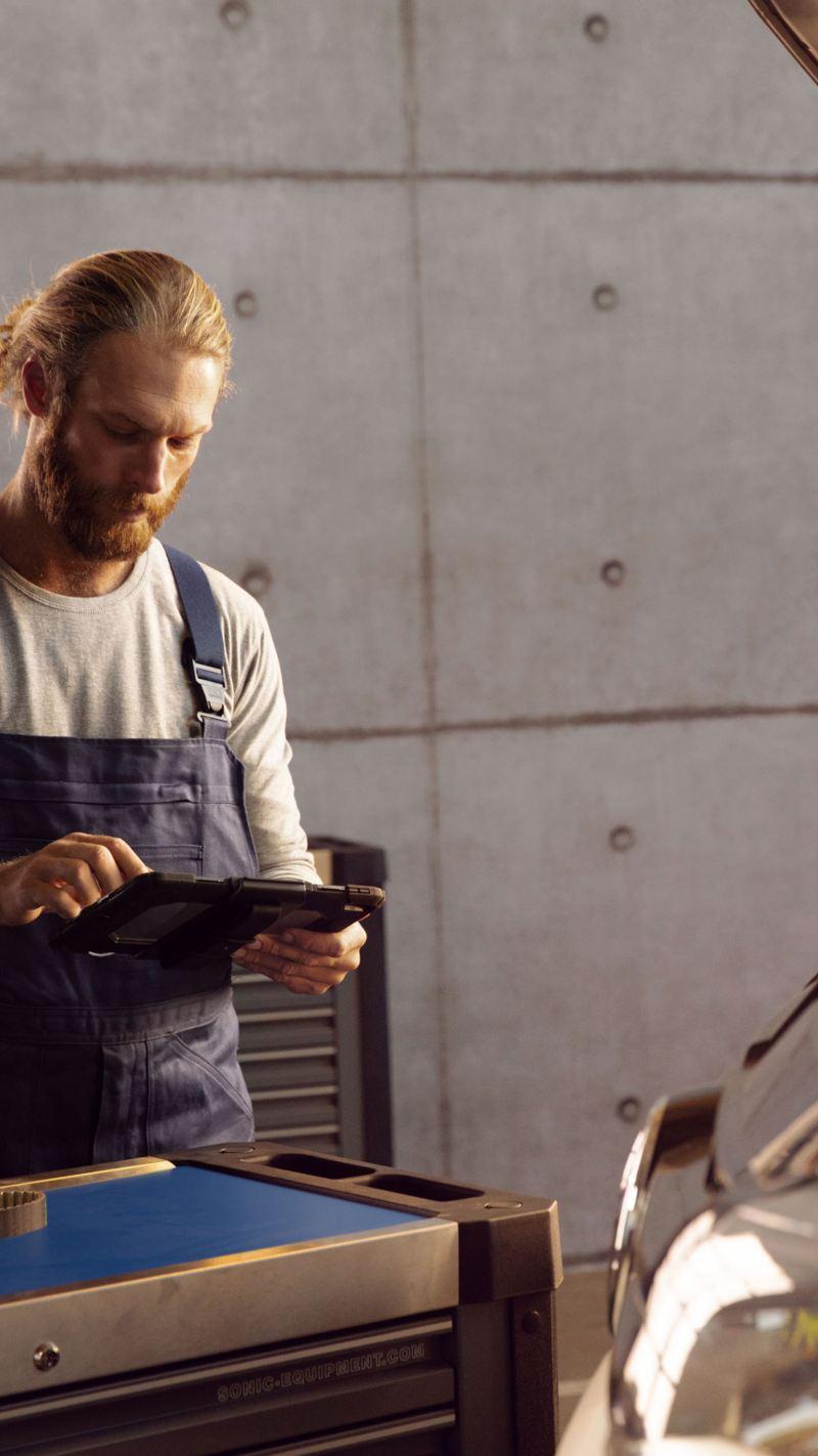 Bildet viser en bilmekaniker som utfører diagnosetest ved hjelp av en iPad av en Volkswagen varebil på et merkeverksted
