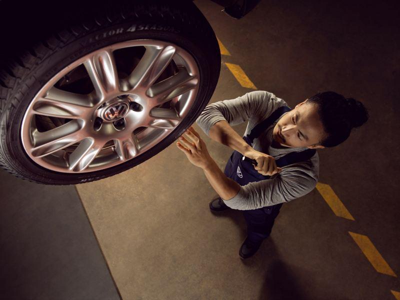 Ein Mechaniker prüft einen montierten Reifen.