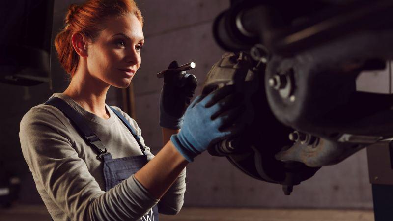 Eine Mechanikerin begutachtet die Bremsscheibe.