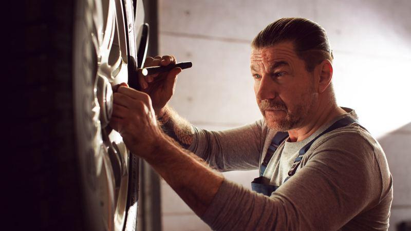 Ein Mechaniker betrachtet den Zustand eines Reifens mit einer Taschenlampe.