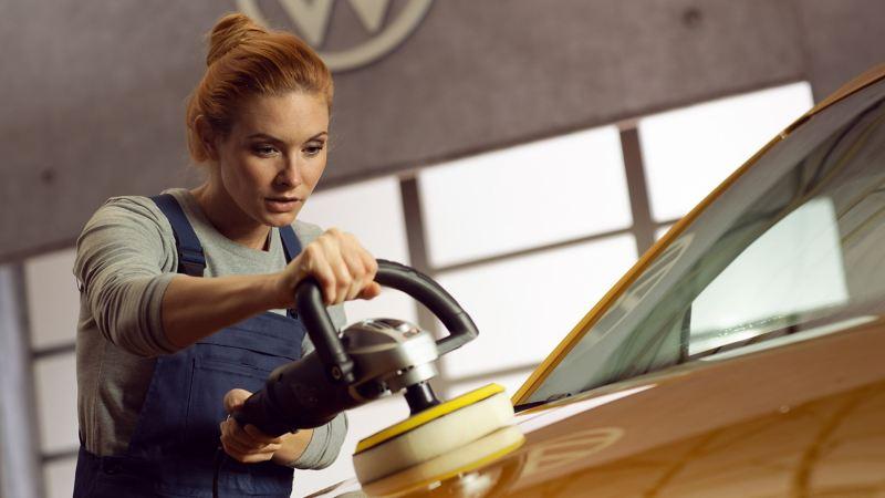 Eine Mechanikerin poliert eine Fahrzeughaube.