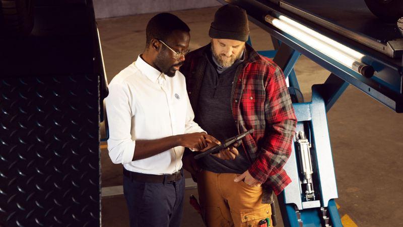 Bildet viser to personer som snakker sammen på et merkeverksted