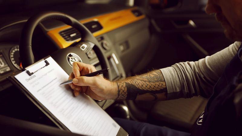 Bildet viser en bilmekaniker som sitter inni en Volkswagen varebil med en sjekkliste for verkstedsgjennomgang på service