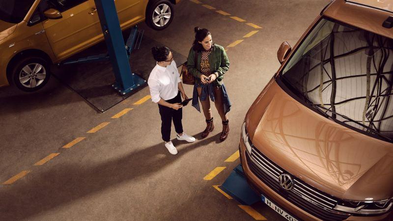 Ein Mann und eine Frau unterhalten sich während einer Schlüsselübergabe für ein Fahrzeug.