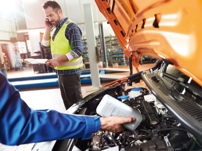 Mechanik przy otwartej masce samochodu