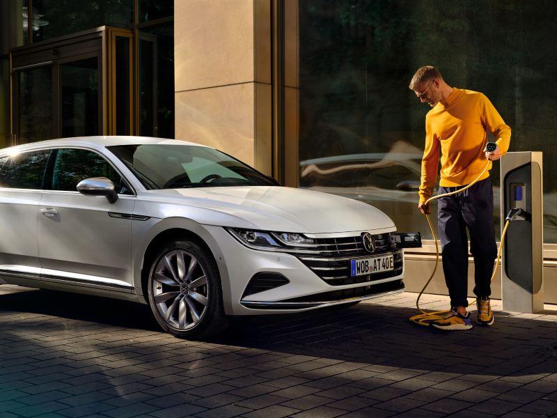 Arteon Shooting Brake e-hybrid, en man står framför bilen och håller i en laddningskabel