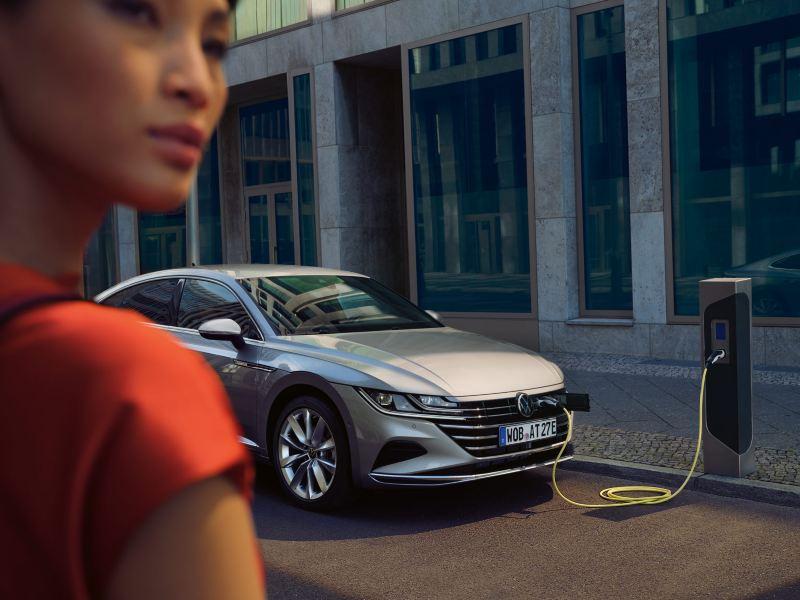 VW Arteon eHybrid står på laddningg, en kvinna som går mot bilen syns först i bild