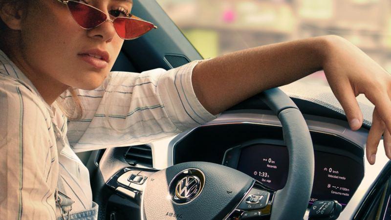 Mujer en interior de auto equipado con sistemas de seguridad Volkswagen ideal para viajar por carretera