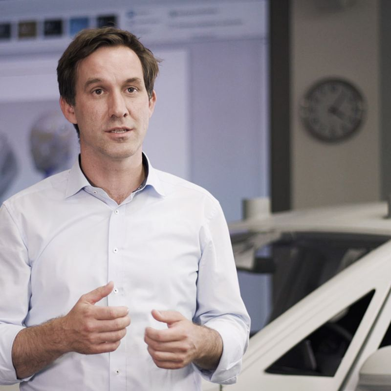 A Volkswagen designer standing in front of a car and screen